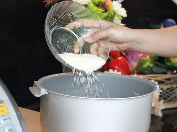 Nên cho từng nắm gạo vào nồi thay vì đổ cả thau 1 lượt